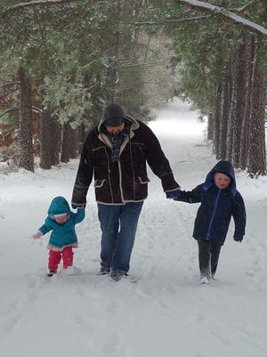 Dutch Bryant walks with his children, Atticus and Norah, in Cumberland Furnace on Friday.
