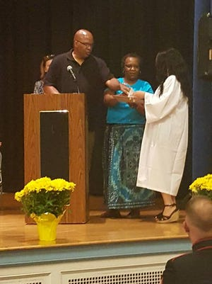 Vandrick and Cynthia Hamlin present a scholarship to Howard High student, Kristen R. Coleman. The scholarship is the first under the Cameron Hamlin Foundation, which honers the Hamlin's son.