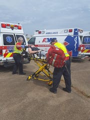 Emergency responders load a victim in Thursday's mock disaster drill into an ambulance.