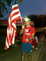 Russ Mathers holds a flag at the 2015 Moving Tribute