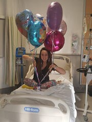 Alexis smiles with balloons before her surgery on Jan. 18.