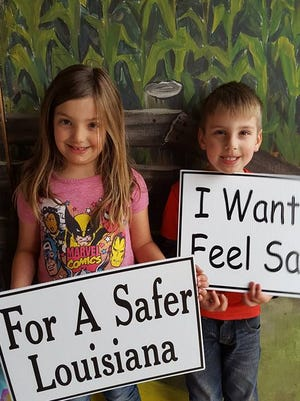 Anna and Thomas Chibnick, the grandchildren of Melinda Allison, hold up signs at the Earth Angel Event