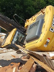 This trackhoe overturned Sunday while tearing down