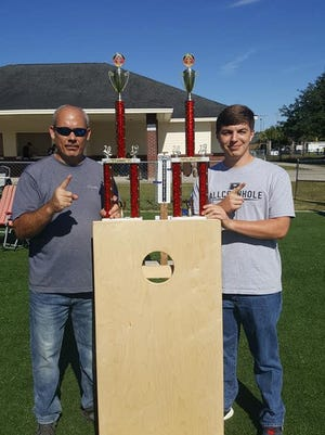 Cornhole doubles partners Chris Pittman, left, and Hunter Yaklin with their trophies for winning a tournament last fall in Hardeeville, S.C.