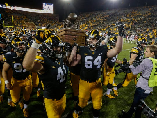 Iowa's Bo Bower, left, and Cole Croston carry the Cy-Hawk Trophy off the field after a 42-3 win over Iowa State on Saturday, Sept. 10, 2016, at Kinnick Stadium in Iowa City.