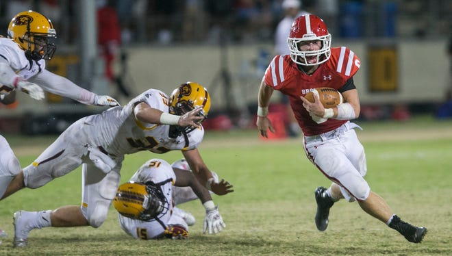Brophy's Noah Pittenger (6) breaks a tackle from Mountain Pointe's Keondre Churchwell (15) and heads toward the endzone at Arizona Phoenix College in Phoenix, AZ on Friday, Oct. 10, 2014. at Arizona Phoenix College in Phoenix, AZ on Friday, Oct. 10, 2014.