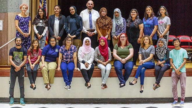 STEM Academy Principal Dante Petretti poses with the top-ranked academic achievers in the 2018 graduating class. The top 18 students are all female.