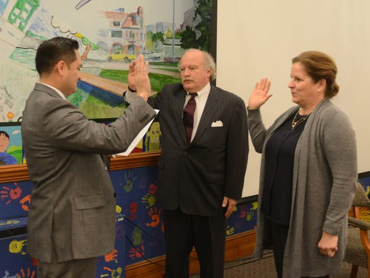 Alfredo Aguilar swearing in trustees James  A. Morgan and Jennie Smith Wilson on Monday to three-year terms on the Ridgewood Board of Education.