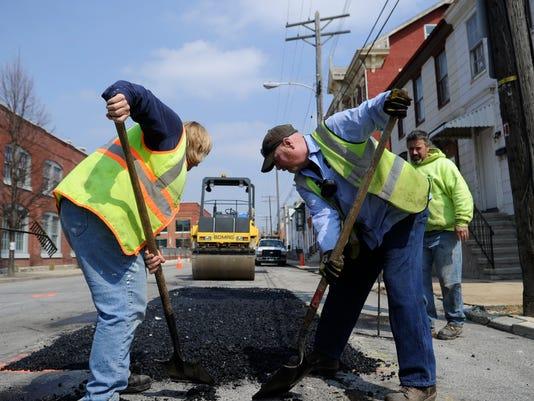 Sherry Saboury, left, and Steve Mundorff with Stewart & Tate Inc. shovel excess asphalt on West Philadelphia Street in April 2011.  (DAILY RECORD/SUNDAY NEWS - KATE PENN)
