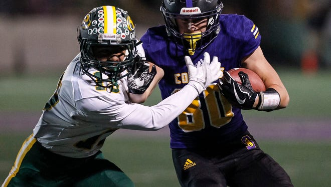Salinas' Jeffrey Weimer fights off a Placer defender during an CIF Football Regionals: Division IV AA-North playoff game between the Salinas Cowboys and the Placer Hillmen of Auburn, CA at Salinas High School on Friday, December 8, 2017 in Salinas, Calif. Vernon McKnight/for The Californian