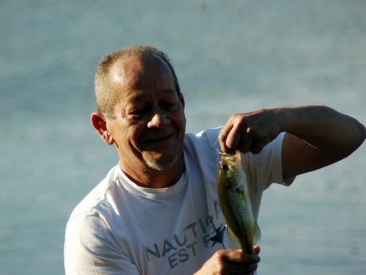 A man takes a close look at a young largemouth bass before releasing it at Gifford Pinchot State Park.