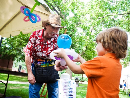 Baloon artist Rob Query hands off a recently constructed alien in a spaceship to Walker Daniels, 4, of Gettysburg at the Gettysburg Festival on in 2014. This year's event, which was scheduled for June 12-14, has been canceled.