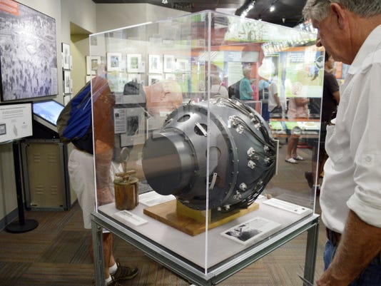 """This Monday, July 13, 2015 photo shows a visitor to the Bradbury Science Museum in Los Alamos, N.M. examines a replica of """"the gadget"""". The gadget was the atomic bomb tested at the Trinity Test Site on July 16, 1945. Thursday marks the 70th anniversary of the Trinity Test in southern New Mexico and comes amid renewed interest in the Manhattan Project thanks to new books, video oral histories and a WGN America television drama series. (AP Photo/Russell Contreras)"""