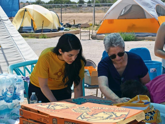 Diana O'Brien, left, and her mother Ann Nieto prepare supplies for the residents of Camp Hope earlier this week where they also helped to hand out pizza for lunch. Camp Hope provides a tent refuge for the homeless on the grounds of Community of Hope on West Amador.