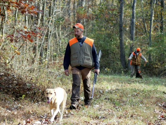 A hunter with his dog is in pursuit of grouse, another quarry of the fall season.