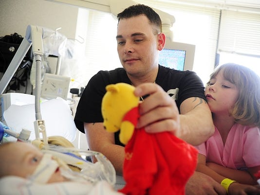Matt Schwartz uses a Winnie-the-Pooh toy to play peek-a-boo with his youngest child Houston, 7 months, as his oldest chidl Lexy, 7, leans against his shoulder on this month in the pediatric intenstive care unit at Penn State Milton S. Hershey Medical Center in Hershey.