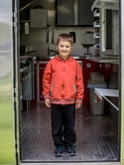 "Eli Lockers, 4, poses on his father's new food truck called ""Eli's Eats."""