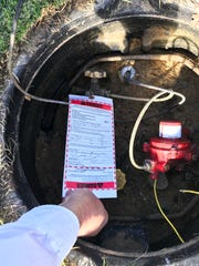 In this provided photo, John Turco displays a danger tag that is attached to the main gas meter at his house in the Quail West community in Naples on Thursday, Jan. 25, 2018. The couple says they were forced out of their house after discovering traces of carbon monoxide and defects in the construction.
