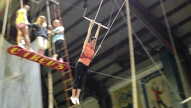 The Adventuress swings on the trapeze wearing a safety rope. The Adventuress, Leslie Bailey, learns to wire walk and swing on the trapeze with the Peru Amateur Circus Thursday June 6, 2013.