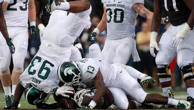 Western Michigan's Jarvion Franklin, bottom, is tackled by Michigan State's Vayante Copeland (13) and Damon Knox (93) during the first quarter of an NCAA college football game, Friday, Sept. 4, 2015, in Kalamazoo, Mich.