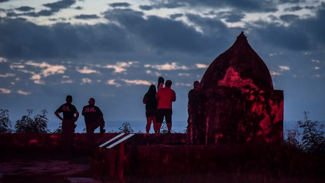 A red light shines on the remnants of Fort Nuestra Señora de la Soledåd, or Fort Soledad, as Guam Fire Department personnel and others overwatch rescue efforts underway for three distressed surfers outside the mouth of Umatac Bay on Friday, Oct. 20, 2017.