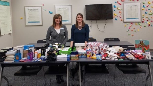 Pictured are Amy Docter and Brooke Vis, Heartland Volunteer coordinators, with items collected for Jacob Kowalski's care package.
