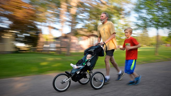 St. Joseph resident Dan Rolfes, 61, runs with his grandson, Noa Hoadley, right, 8, and newest grandchild, Oliver Sunsdahl, 8 months, in a baby jogger Wednesday, May 18, in St. Cloud. Rolfes started running with Noa during the Earth Day Half Marathon when Hoadley was just a baby. This year, Hoadley ran in the kids' event and now Rolfes has started the tradition again, running with his infant grandson, Oliver Sunsdahl. Rolfes and Oliver will run in the STRIDE 5K on Friday, May 20.