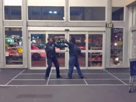 A Detroit Police officer and private citizen are seen on a video taken by an onlooker at Meijer on 8 Mile Rd. in Detroit, Mich., Sunday, October 8, 2017.