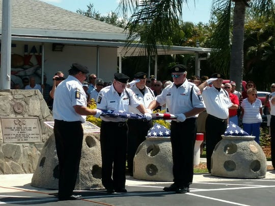 An honor guard folds an American flag to present to Theodore Robbins, standing in for the families of four missing B-52 bomber crew. The crew crashed during a World War II training exercise 40 miles off the coast of Fort Myers Beach. Monday's ceremony was the first time they'd been publicly recognized for their service.