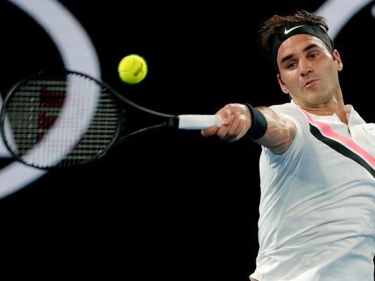 Switzerland's Roger Federer makes a forehand return to Germany's Jan-Lennard Struff during their second round match at the Australian Open tennis championships in Melbourne, Australia, Thursday, Jan. 18, 2018. (AP Photo/Vincent Thian)