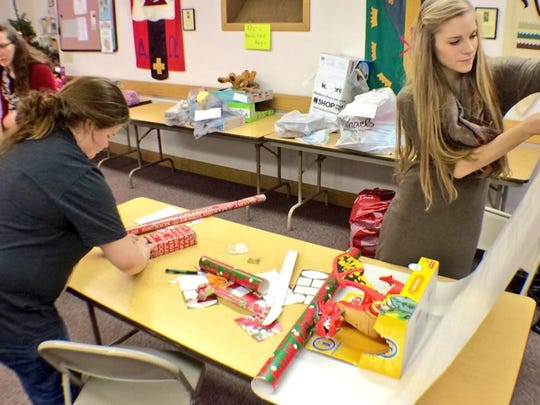 Members of Frame Memorial Presbyterian Church's youth group wrap presents Wednesday for the Holiday Basket Project.