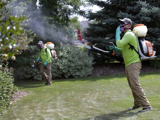 Ben Wettengel and Larry Hren, applicators with Mosquito Squad, work their way through a client's yard as they spray a permethrin-based mosquito repellent in Appleton.