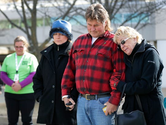 Ben Rozelle of Neenah holds hands with his wife Betsy