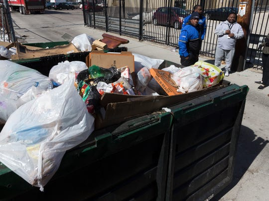 """Assistant district attorney Catelin Ringersma (second from from right) and others take note of a trash violation  during a """"blight sweep"""" to take note of problems that need to be dealt with Wednesday, March 14, 2018 on the near West Side of Milwaukee, WIs. Since 2000, the Milwaukee County district attorney's office has stationed prosecutors in city neighborhoods. Each prosecutor works in tandem with a police officer and a community organizer. The teams focus on blight and take action designed to improve quality of life, such as shutting down drug houses, holding absentee landlords accountable and making sure taverns follow the rules. At its height, there were seven Community Prosecution Units, one in each police district. Now, there are three.  L"""