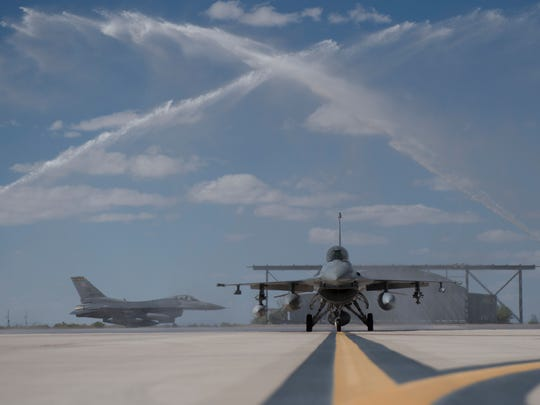 Two F-16 Fighting Falcons taxi under an arch of water as they arrive at Holloman Air Force Base, N.M., to join the 8th Fighter Squadron Sept. 21, 2017. These F-16s were part of the final six-ship formation from Hill Air Force Base, Utah, as they prepare for the F-35 Lighting II training mission. These last six aircraft are part of Holloman's role to support Air Force fighter pilot training.