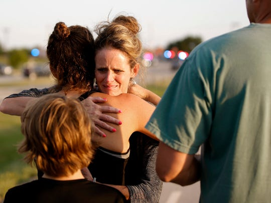 Jennifer Stong hugs Tasha Hunt outside the scene of