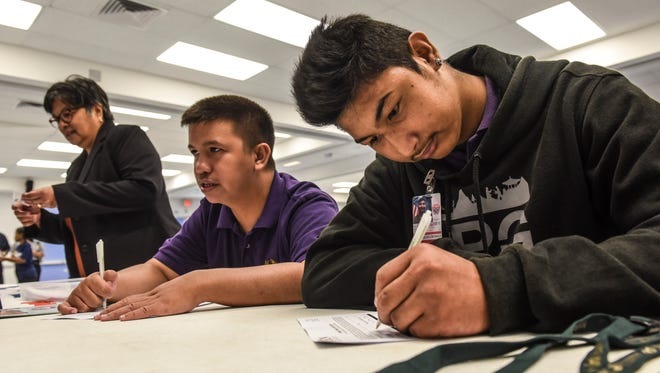 Daniel John Blas, right, and David Ash Rosario, fill out employment applications during a customized employment fair at the Guam Community College for persons with disabilities.