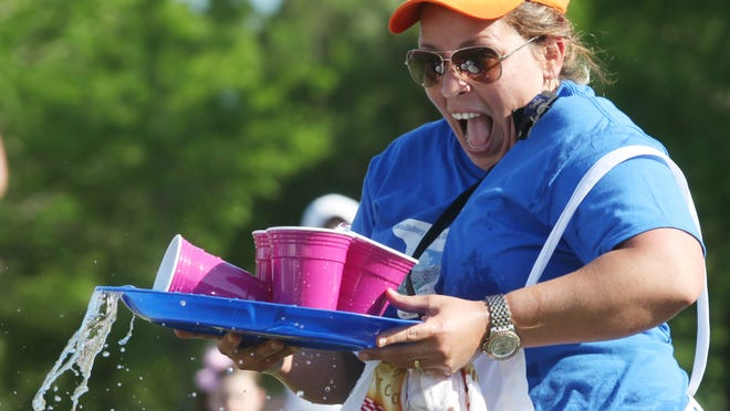 Lea Collier, of the Holiday Inn Express and Suites at The Forum, reacts after spilling water during the Waiter and Waitress race that was part of the Southwest Florida Travel Rally at Lakes Park on Wednesday.