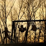 Children swing and run on a playground at sunset in Armstrong Park in Lafayette, Ind. Playground concussions are on the rise, a government study says.