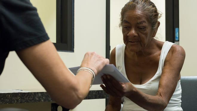 Maria Moreno, 58, takes a voucher from the Homeless ID Project to pay for her ID on June 6, 2018 at the Human Service Campus in downtown Phoenix.