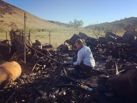 Stacy Hyatt sorts through the remains of her home in Wheeler Canyon after the Thomas Fire destroyed the property she was renting.
