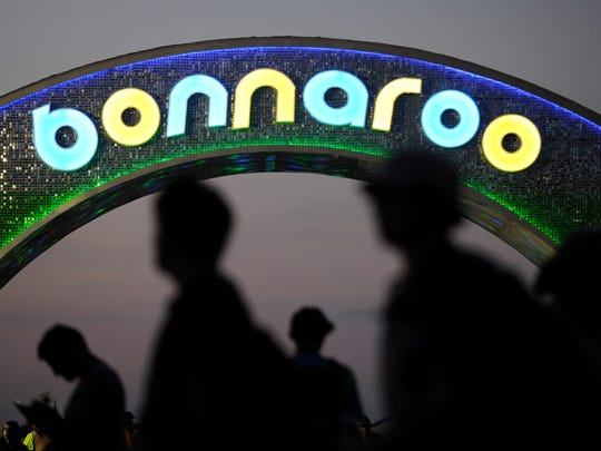 Attendees walk past the Bonnaroo Arch at dusk on Saturday,
