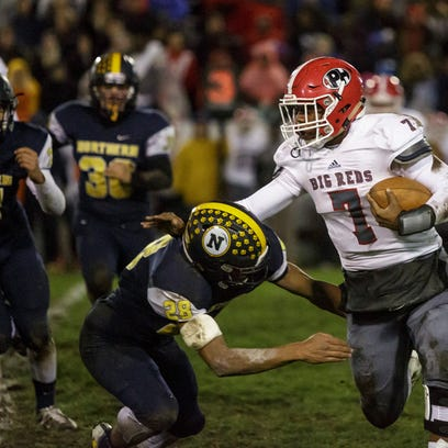Port Huron Northern's Theo Ellis hands off the ball to Tyler Lee during the Crosstown Showdown Friday, Oct. 21, 2016 at Memorial Stadium in Port Huron.
