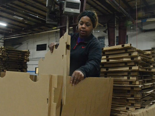 Battle Creek resident Shakeda Brown, 33, assembles packaging Wednesday at One Earth Co. at 5701 W. Dickman Road in Battle Creek.