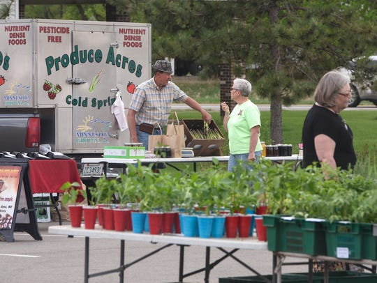 Shoppers look through plants and fresh produce Friday,