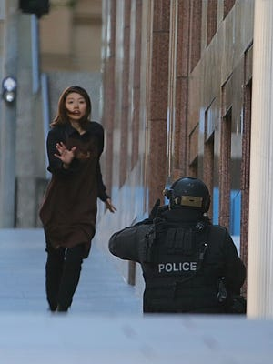 A hostage fleeing from a cafe under siege runs towards an armed tactical response police officer at Martin Place in the central business district of Sydney, Australia, Monday, Dec. 15, 2014. New South Wales state police would not say what was happening inside the cafe or whether hostages were being held. But television footage shot through the cafe's windows showed several people with their arms in the air. (AP Photo/Rob Griffith)