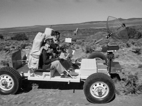 """This 1971 image provided by NASA shows Apollo 17 astronauts, Harrison """"Jack"""" Schmitt, left, and an unidentified man, training with the lunar roving vehicle on the Big Island of Hawaii. Before many Apollo astronauts went to the moon, they came to Hawaii to train on the Big Island's lunar landscapes. Now, decades-old photos are surfacing of astronauts scooping up Hawaii's soil and riding across volcanic fields in a """"moon buggy"""" vehicle."""