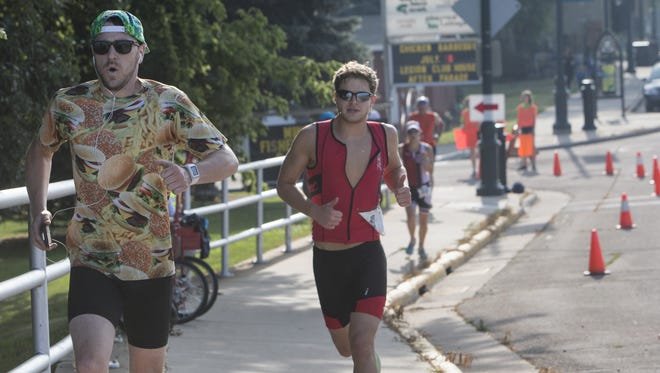 Competitors run toward the Winneconne bridge in the Winnebago County Triathlon in Winneconne on July 12, 2015.