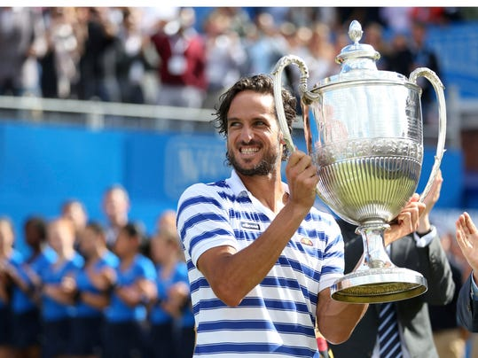 Spain's Feliciano Lopez celebrates with the trophy after winning the final against Croatia's Marin Cilic, left, at The Queen's Club tennis tournament in London, Sunday June 25, 2017. (Steven Paston/PA via AP)