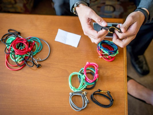 Red Lion Area Senior High School student Devin Morton shows off the handmade bracelets his company Morton Bracelets produces before giving his business pitch to a panel at York College on April 13. Morton sells his bracelets, which come in leather or paracord, online.